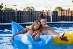 Sisters floating in the pool Stock Photos