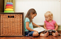 Sisters on the floor reading a book Royalty Free Stock Images