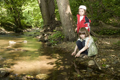 Sisters by the forest creek Royalty Free Stock Photo