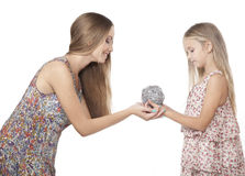 Sisters friendship and love. Sister giving a little girl a gift. Stock Photography