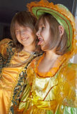 Sisters by fun in carnival clothes Royalty Free Stock Photos