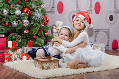 Sisters with gifts at Christmas tree Royalty Free Stock Photos