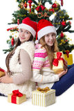 Sisters with gifts under Christmas tree Stock Photo