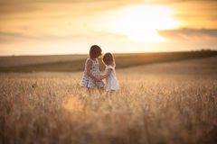 Sisters girls walk in the field with rye sunset Stock Photos