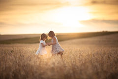 Sisters girls walk in the field with rye sunset Royalty Free Stock Photos