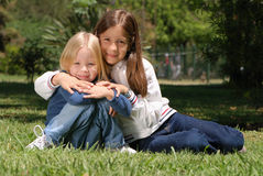 Sisters on a glade in park Royalty Free Stock Photo