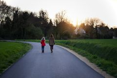 The sisters go along the empty road in the evening. Village life stock photography