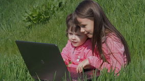 Sisters on green grass with laptop. Little girls in the park on a sunny day. Happy children in nature on a sunny day stock video