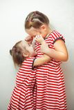 Sisters with hairstyles and same dresses having fun royalty free stock photos