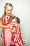 Sisters with hairstyles and same dresses having fun stock photography