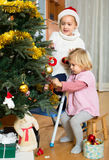 Sisters hanging decorations on fir Royalty Free Stock Photography