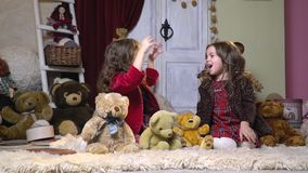 Two sisters look at each other and shout joyfully, sitting among the plush toys, slow motion stock video footage