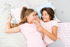 Sisters happy small kids relaxing in bedroom. Friendship of small girls. Leisure and fun. Having fun with best friend. Children playful cheerful mood having royalty free stock photo