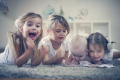 Sisters have play with baby brother in living room. On the move Royalty Free Stock Photography