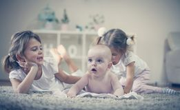 Sisters have play with baby brother. Three children at home Royalty Free Stock Photos