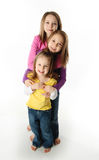 Sisters having fun. Three cute young sisters hugging each other, isolated on white Royalty Free Stock Photography