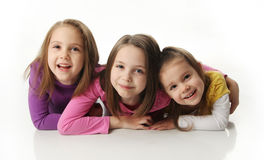 Sisters having fun. Three cute young sisters hugging each other, isolated on white Stock Photos