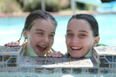 Sisters Having Fun in a Swimming Pool Outdoors. Two Sisters Having Fun in a Swimming Pool Laughing Royalty Free Stock Images