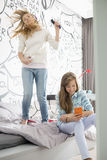 Sisters having leisure time in bedroom Royalty Free Stock Photography