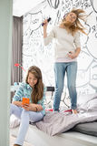 Sisters having leisure time in bedroom Stock Photos