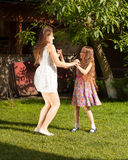 Sisters having party and dancing on grass at yard Stock Images