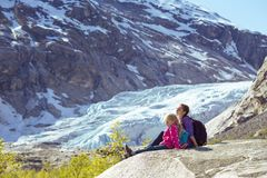 Sisters hiking and the glacier. Sisters hiking at the mountains and the glacier Nigardsbreen at the background. ecology and global warming royalty free stock photography