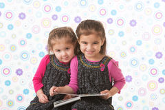 Sisters holding book. Portrait of sisters sitting close together with book in hand Royalty Free Stock Images
