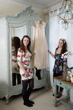Sisters holding dress hanged on hanger Royalty Free Stock Image