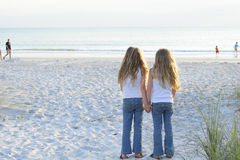 Sisters holding hands on the beach. Shot of sisters holding hands on the beach Stock Photo