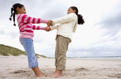 Sisters (5-9) holding hands on beach, low angle view stock photo