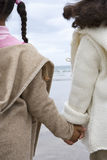 Sisters (5-9) holding hands on beach, rear view stock photos