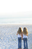 Sisters holding hands on the beach vertical Stock Photos