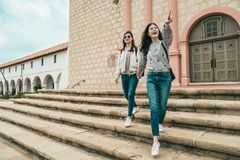Sisters holding hands walking down the stairs stock photo