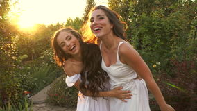 Sisters hug and laugh. Two sisters in white dresses in the garden at sunset. The girls hug and laugh. Family relationships stock video footage