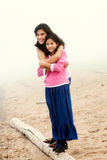 Sisters hugging on foggy beach Royalty Free Stock Images