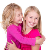 Sisters hugging and looking at each other. Isolated on white Royalty Free Stock Photography
