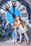 Sisters hugging next to the clock. Christmas Eve. Royalty Free Stock Image