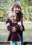 Sisters Hugging - Vertical Stock Photo