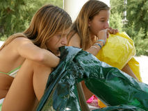 Sisters inflate beach toys. Sisters - best friends  inflate beach toys - mattress and be ready for summer. Horizontal color photo Royalty Free Stock Image