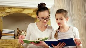 Sisters with interest spending time after book reading, girls spend free time together stock footage
