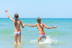 Free Sisters Joyfully And Happily Run Into The Sea On A Hot Sunny Day Royalty Free Stock Photos - 190212448