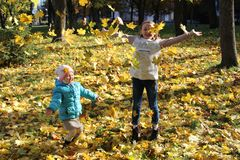 Sisters jump on yellow leaves in autumn park. Happy childhood stock photo