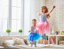 Sisters jumping on the bed. Two cute children baby girls playing and having fun in the kids room. loving sisters jumping on the bed Royalty Free Stock Photo