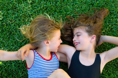 Sisters kid girls smiling lying on garden grass royalty free stock photography
