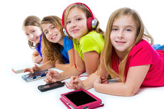 Sisters kid girls tech tablets and smatphones. Sisters cousins kid girls with tech tablets and smatphones in a row lying on white background stock photos