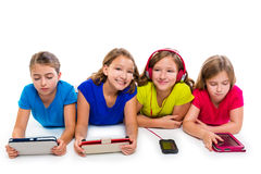 Sisters kid girls tech tablets and smatphones. Sisters cousins kid girls with tech tablets and smatphones in a row lying on white background Stock Photography