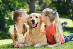 Sisters kissing their dog in the park Royalty Free Stock Images