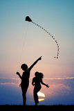 Sisters with kite at sunset Stock Image