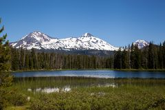 The Sisters and Lake Scott. A tranquil Northwest lake reflects the Sisters in the Oregon Cascades, near Bend Oregon on a perfect summer day in the wilderness of Royalty Free Stock Photography