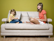 Sisters with laptops on sofa Stock Image